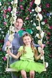 Pai e menina de sorriso com o trevo na cabeça no balanço Fotografia de Stock Royalty Free