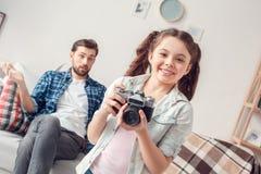 Pai e menina pequena da filha em casa que tomam as imagens que olham a câmera pai curioso que senta-se no sofá confundido imagem de stock