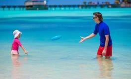 Pai e menina que jogam com o disco do voo na água pouco profunda na praia Fotos de Stock