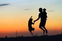 Pai e miúdos que saltam no por do sol Fotografia de Stock Royalty Free
