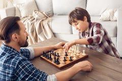 Pai e pouco filho em casa que sentam-se na tabela que joga parte movente do menino da xadrez pensativa imagem de stock royalty free