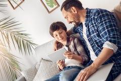 Pai e pouco filho em casa que sentam-se no paizinho do sofá com o portátil que abraça o menino que joga a tabuleta digital alegre fotos de stock royalty free