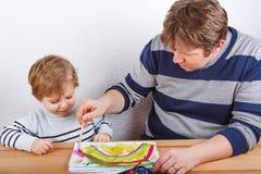 Pai e rapaz pequeno de dois anos que têm a pintura do divertimento Imagens de Stock