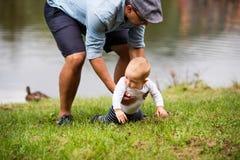 Pai e rapaz pequeno pelo lago no verão Imagens de Stock