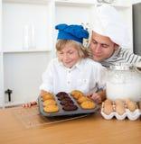 Pai e seu filho que apresentam seus queques Imagem de Stock Royalty Free