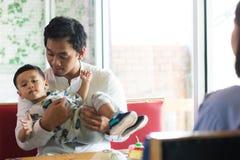 Pai e seu filho que jogam no caf? na manh? foto de stock