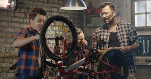 Pai e seus dois filhos que reparam uma bicicleta video estoque