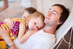 Pai e seus miúdos que relaxam no hammock fotografia de stock