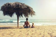 Pai e sua ioga praticando do filho da criança na praia Sentam-se na pose dos lótus sob o guarda-chuva de sol grande do bastão e o foto de stock royalty free