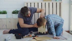Pai farpado e filho bonito pequeno que fazem o aviário de folhas de madeira em casa Fazer do conceito da infância e da paternidad filme