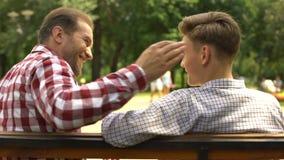 Pai farpado que comunica-se com o filho adolescente, sentando-se no banco no parque, confiança vídeos de arquivo