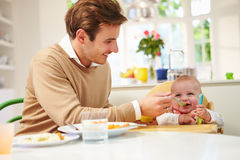 Pai Feeding Baby Sitting na cadeira alta em horas de comer Fotografia de Stock