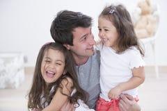 Pai feliz com as filhas que passam o tempo da qualidade junto em casa Imagens de Stock