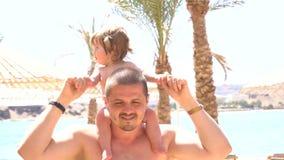 Pai feliz com a filha bonito em seu pescoço vídeos de arquivo