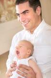 Pai feliz com a filha de bocejo nas mãos Fotografia de Stock