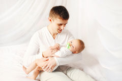 Pai feliz com o bebê em horas de dormir da casa da cama Fotos de Stock Royalty Free