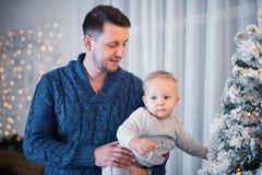 Pai feliz com sua posição de um ano bonito do filho perto da árvore de Natal fotografia de stock royalty free