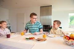 Pai feliz com suas crianças que falam no café da manhã em casa foto de stock royalty free