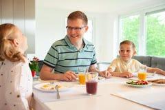 Pai feliz com suas crianças que falam no café da manhã em casa imagens de stock