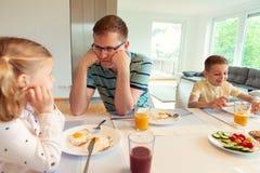 Pai feliz com suas crianças que falam no café da manhã em casa fotografia de stock royalty free