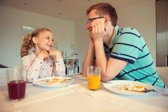 Pai feliz com suas crianças que falam no café da manhã em casa fotos de stock royalty free