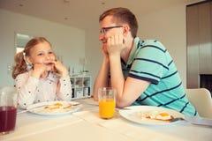 Pai feliz com suas crianças que falam no café da manhã em casa fotos de stock