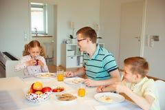 Pai feliz com suas crianças que falam no café da manhã em casa fotografia de stock