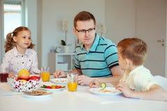 Pai feliz com suas crianças que falam no café da manhã em casa imagem de stock royalty free