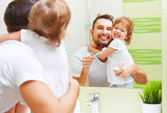 Pai feliz da família e menina da criança que escova seus dentes no bathroo Fotografia de Stock