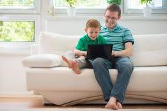 Pai feliz e criança que jogam em casa foto de stock