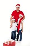 Pai feliz e duas filhas no riso dos chapéus de Santa imagens de stock royalty free