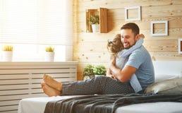 Pai feliz e filha da família que riem e que jogam na cama imagens de stock