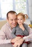 Pai feliz e filha em casa que sorriem Imagem de Stock Royalty Free