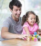 Pai feliz e filha que jogam com blocos de apartamentos na tabela na casa Foto de Stock