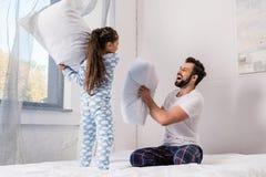 pai feliz e filha que jogam a luta de descanso na cama imagem de stock royalty free