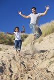 Pai feliz e filha que saltam na praia Fotografia de Stock