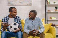 pai feliz e filho adulto com bola de futebol que sorriem-se ao sentar-se fotografia de stock royalty free