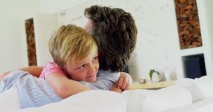 Pai feliz e filho que abraçam-se na sala de visitas 4k vídeos de arquivo