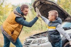 pai feliz e filho que dão a elevação cinco ao reparar o carro imagens de stock royalty free