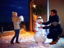 Pai feliz e filho que fazem o boneco de neve na luz da noite fotografia de stock royalty free