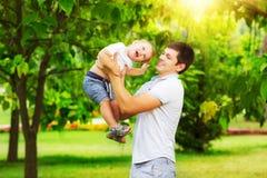 Pai feliz e filho que jogam junto ter o divertimento na SU verde Fotografia de Stock