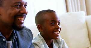 Pai feliz e filho que têm o divertimento na sala de visitas video estoque