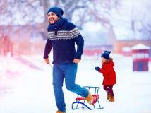Pai feliz e filho que têm o divertimento com o pequeno trenó sob a neve do inverno Fotos de Stock Royalty Free