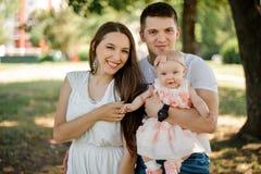 Pai feliz e mãe novos que andam com o bebê bonito na paridade fotos de stock royalty free