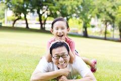Pai feliz e menina que encontram-se na grama Imagens de Stock