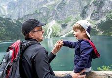 Pai feliz e seu filho que têm o divertimento perto do lago Foto de Stock Royalty Free