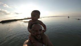 Pai feliz e seu filho que tomam um selfie junto na praia Sorriso video estoque