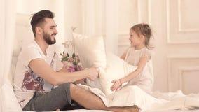 Pai feliz e sua filha pequena que têm o divertimento na cama video estoque