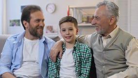 Pai feliz e vovô que abraçam o menino, sentando-se no sofá em casa, olhando a câmera video estoque