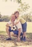 Pai feliz novo e 7 ou 8 anos entusiasmado do filho idoso que joga junto o futebol do futebol no jardim do parque da cidade que le Foto de Stock